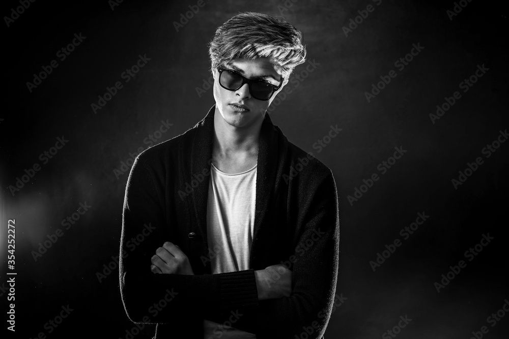 Fototapeta Trendy young man with cool hairstyle wearing black jacket with sunglasses. High Fashion male model posing on black background. Art design concept