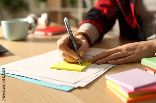 Student girl hand writing on post note at night Fototapeta
