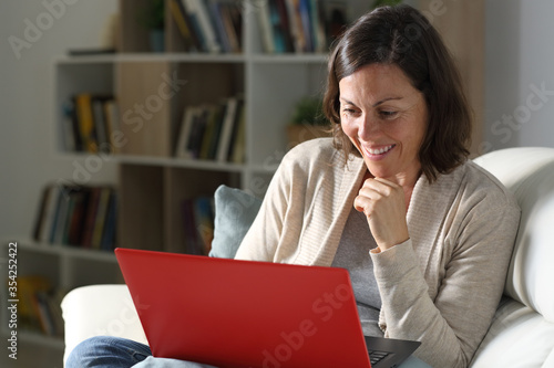 Happy adult lady streaming content on laptop at night at home Canvas Print