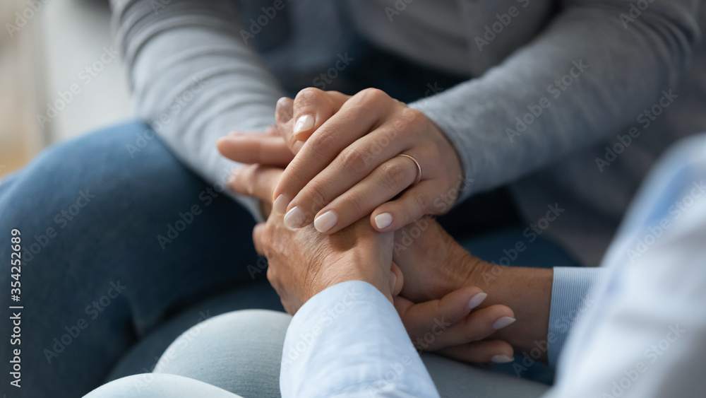 Fototapeta Adult daughter comforting old mom strokes holds her hand close up view. Strong connection confidential conversation, empathy and mercy, support in hard life period, be near sharing heart pain concept
