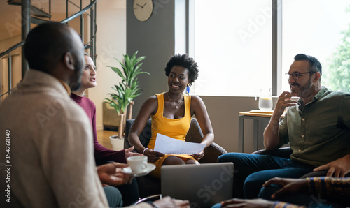 Fotografiet Group of diverse businesspeople smiling during a casual meeting