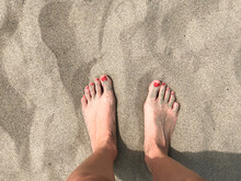 Two Female Feet On Sand Close-...