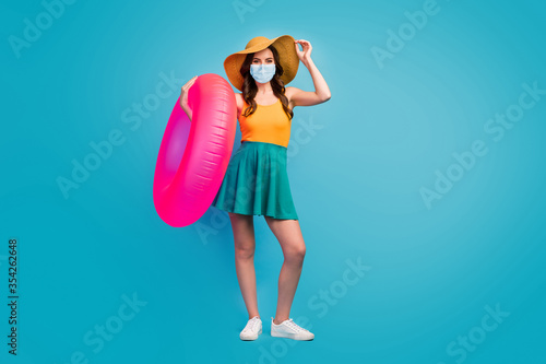 Obraz Full length body size view of her she pretty lady hold pink rubber ring wear mask public place social distance visit poolside isolated over bright vivid shine vibrant blue color background - fototapety do salonu