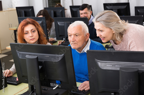 Elderly people working together on computer Fototapete