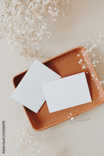 Obraz Blank paper cards with mockup copy space on plate and gypsophila flowers on beige background. Minimal business brand template. Flat lay, top view. - fototapety do salonu