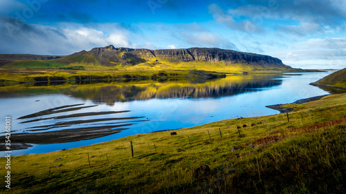 Obraz tranquil scene with view over harsh cliffs illuminated by sunshine that are reflecting in the smooth water outside at the icelandic fjord alftafjördur at snaefellsnes - fototapety do salonu