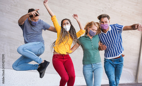 Fotografiet Young people having fun around city street during coronavirus outbreak - Happy f