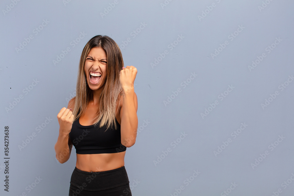 Fototapeta young pretty woman shouting triumphantly, laughing and feeling happy and excited while celebrating success