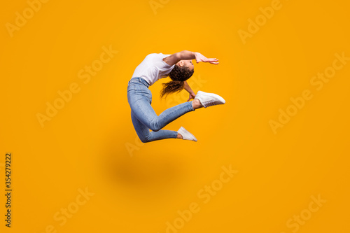Obraz Full size profile photo of amazing lady flexible body bending spine artist dancer performance jumping high wear white t-shirt jeans isolated yellow bright color background - fototapety do salonu