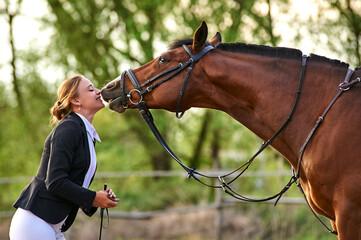 Horse rider girl and horse on a farm. horse kisses a girl.