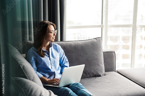 Fototapeta Image of woman working with laptop and smiling while sitting on couch obraz