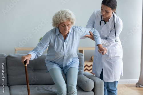 Fototapeta Caring young nurse helping to elderly disabled with walking cane woman get off the couch, age related disease, after illness or operation. Caregiving, provides physical support to old patient concept obraz
