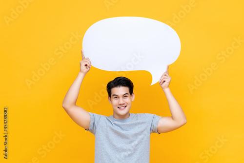 Fototapeta Smiling handsome Asian man holding speech bubble overhead