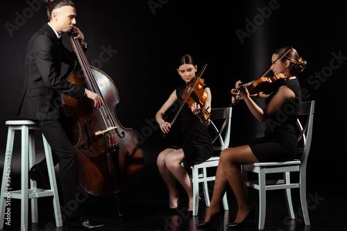 Tablou Canvas trio of professional musicians playing on musical instruments on dark stage