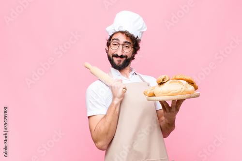 Obraz na plátně young crazy baker man holding bread against pink wall