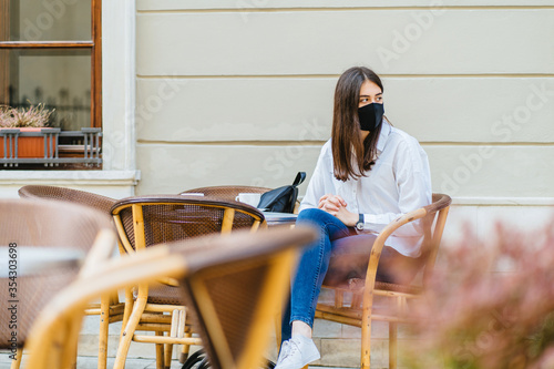 Photo Young woman in facial mask sitting on the cafe terrace alone