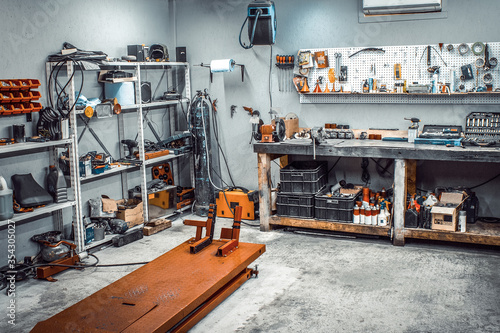 Obraz Garage, service area for disassembling, repairing motorcycles, car service station. Inside the workshop with large workbench, shelving, moto lift, tools kit for processing wrenches on the wall - fototapety do salonu