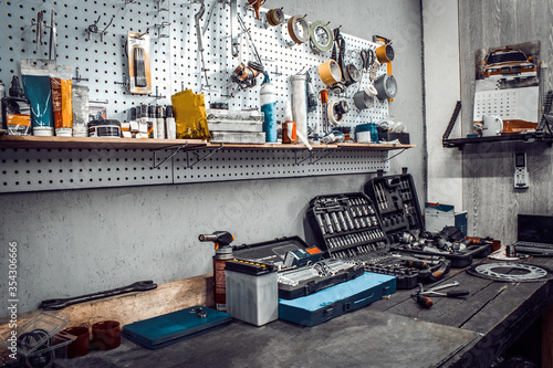 Obraz Inside the workshop. Large workbench and tools kit for working on the table close-up. Workspace for mechanic with wrenches, pliers on a metal wall. Garage for motorcycle repair, car service station. - fototapety do salonu