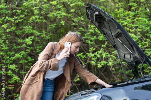 Helpless woman driver calling for help/assistance looking at broken down car, stopped at the roadside Canvas Print