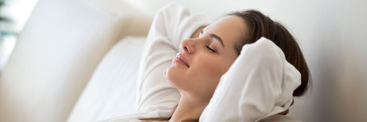 Serene woman leaned on comfy sofa put hands behind head resting in living room close up, enjoy carefree free day, breathing fresh air feels peaceful. Horizontal photo banner for website header design