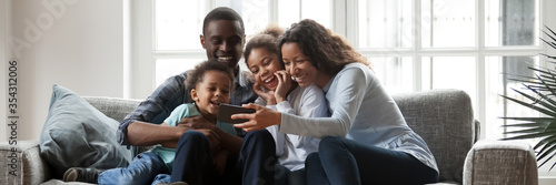 Stampa su Tela Full African family with little kids sit on couch in living room having fun using smart phone new cool application, taking selfie, watch funny videos