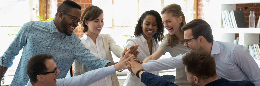 Fototapeta Happy multi ethnic colleagues celebrating business success giving high five show support share common victory. Teambuilding, teamwork, unity concept. Horizontal photo banner for website header design