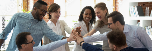 Happy multi ethnic colleagues celebrating business success giving high five show support share common victory. Teambuilding, teamwork, unity concept. Horizontal photo banner for website header design