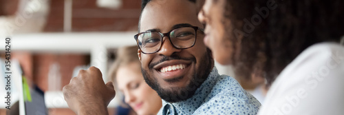 Diverse employees working in shared office focus on african guy flirting with female colleague, teammates friendly conversation good relation concept. Horizontal photo banner for website header design
