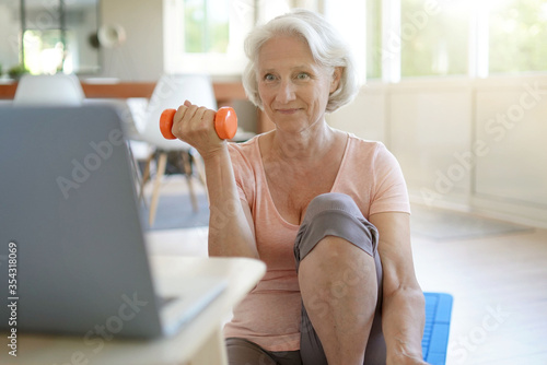 Senior woman doing fitness exercises at home through virtual class Fotobehang
