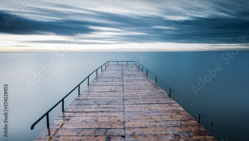 Cuadros en Lienzo Empty wooden pier over blue sea with a sky background