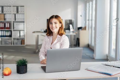 Fototapeta Smiling young friendly businesswoman at her desk obraz na płótnie