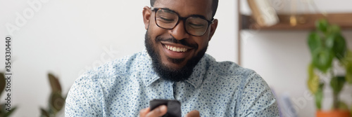 Obraz Smiling African businessman sit at workplace holding mobile phone, texting sms, browsing internet. Distant communication, virtual chat usage concept. Horizontal photo banner for website header design - fototapety do salonu