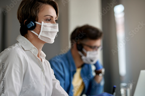Fotomural Call center agent wearing protective face mask while working during virus epidemic