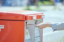 郵便ポストに封筒を入れる若い女性の手元
