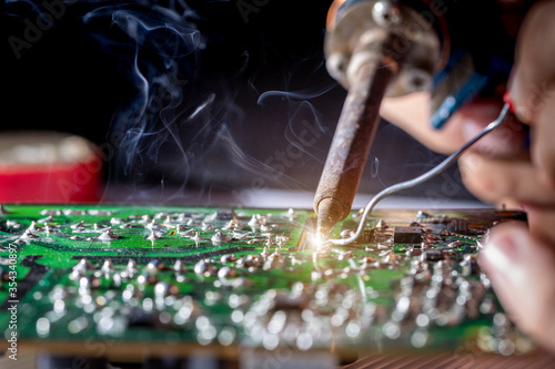Fotografia Technician repair electronic circuit board with soldering iron and tin wire