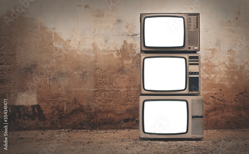 Photo Retro old televisions cut out screen pile on floor in front of old wall background