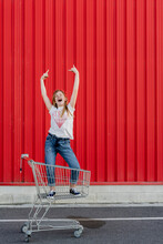 Girl Rocking In A Shopping Cart In Front Of Red Wall