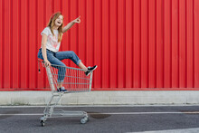 Girl In A Shopping Cart In Fro...
