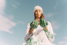 Young Woman Looking Down On Her Green Painted Hands