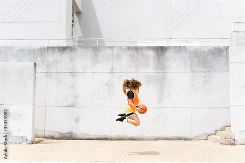 Teenage girl jumping with basketball outdoors