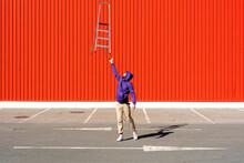 Young Man Balancing A Ladder I...