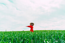 Happy Woman Wearing Red Dress And Straw Hat Standing On A Field