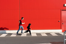 Man Running Together With His Little Girl Wearing Black Fancy Dress On Zebra Crossing