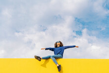 Happy Young Woman Sitting On Yellow Wall Against Cloudy Sky Looking Up