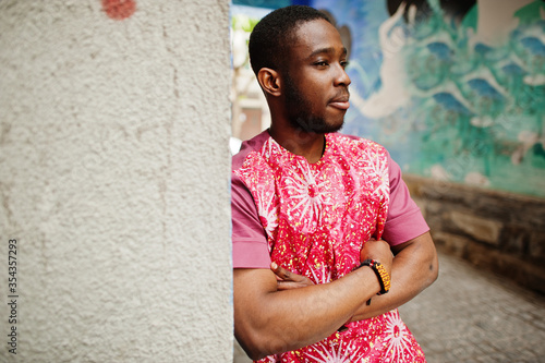 Fototapeta Portrait of a black young man wearing african traditional red colorful clothes. obraz