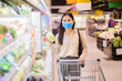 Leinwandbild Motiv woman is shopping in supermarket with face mask