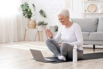 Smiling Senior Woman Training At Home Online Via Laptop, Waving At Camera