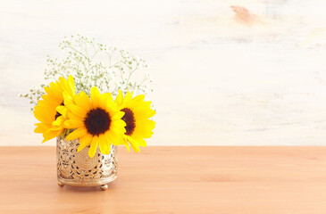 Top view image of sunflowers over wooden table and white background
