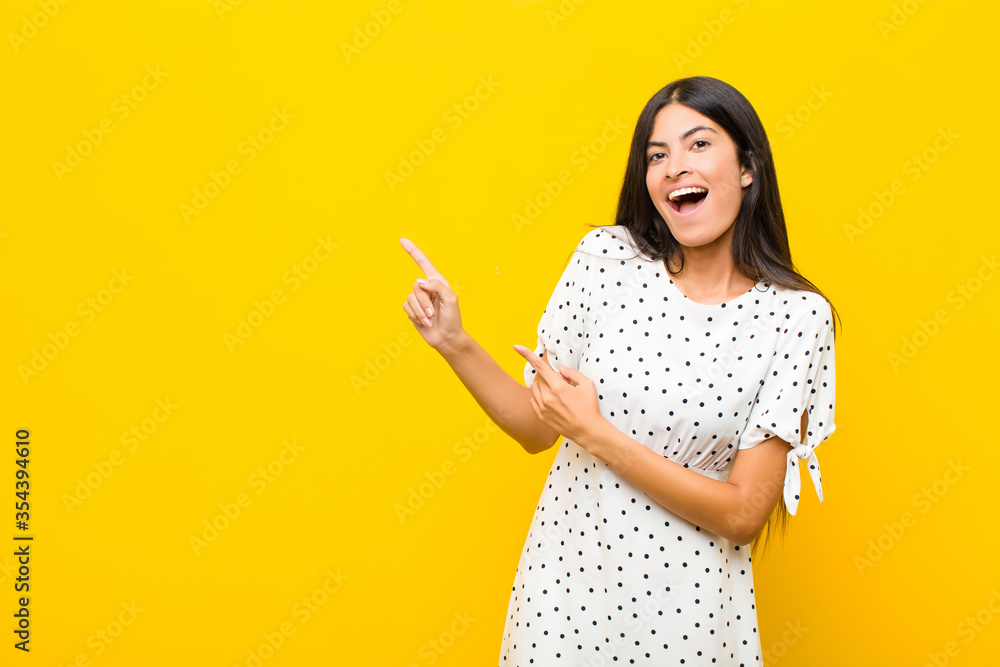 Fototapeta young pretty latin woman feeling joyful and surprised, smiling with a shocked expression and pointing to the side against flat wall