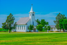 A Small Old Fashioned White Chapel Sits In A Peaceful Green Meadow In Texas.